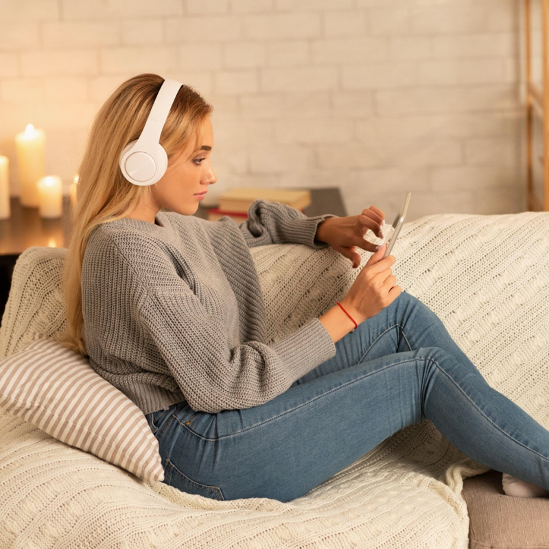 woman on couch streaming on her tablet