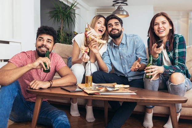Four Friends Watching TV Enjoying Pizza and Beverages