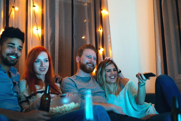 Four Friends Watching TV Together with Popcorn