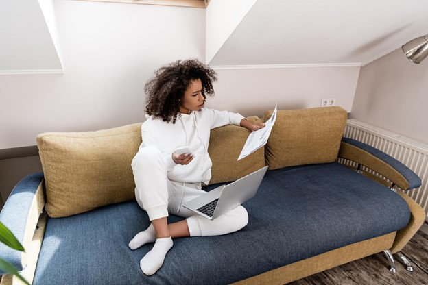Young woman working remotely and sitting on the couch with laptop