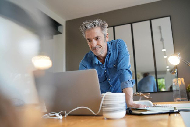 man in an office standing at desk look at laptop